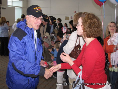 Photo of a World War II veteran greeting passengers at Washington Dulles Airport